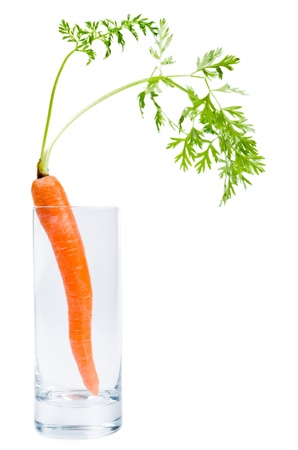 consciously: a carrot stands in a glass before white background