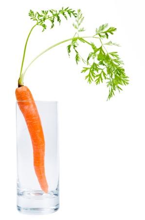 abstinence: una carota si trova in un bicchiere prima di sfondo bianco