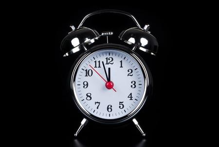 isolates: an oldfashioned alarm clock isolates before black background Stock Photo