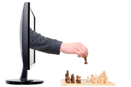 a hand coming from a computer plays chess photo