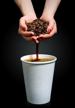 stark: Kaffee fliesst aus einer Handvoll Bohnen in einen Pappbecher Lizenzfreie Bilder