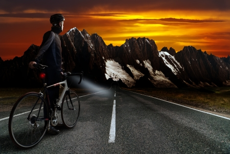 a racing cyclist stands on the street before mountainous region with dusk