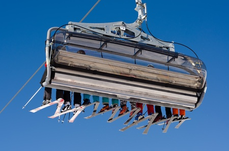 coldly: a ski lift with eight skiers before blue sky