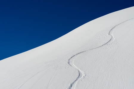 Ski trace in the snow with blue sky photo