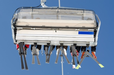 jailer: a ski lift with skiers before blue sky