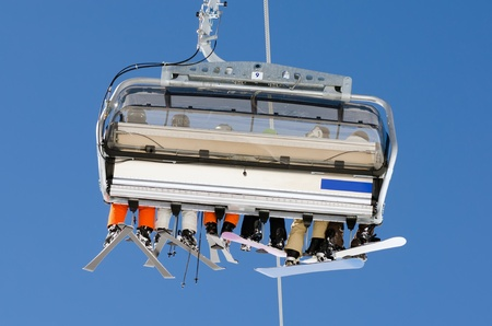 coldly: a ski lift with skiers before blue sky