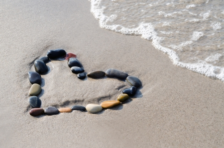 a heart of stones in the surge on the beach photo