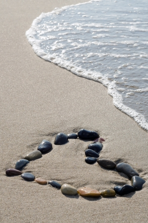 valentine s day beach: a heart of stones in the surge on the beach