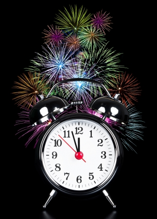 alarm clock at high time with fireworks on black background photo