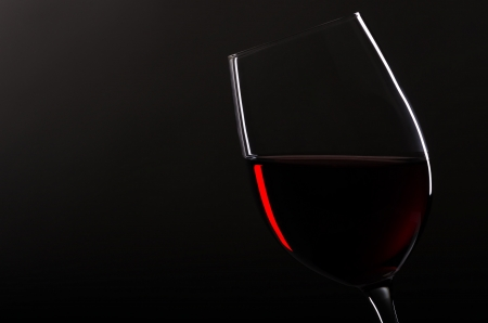 redwine: one wineglass with redwine before black background