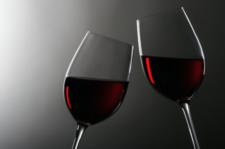 glass of red wine: two wineglasses with redwine stay together