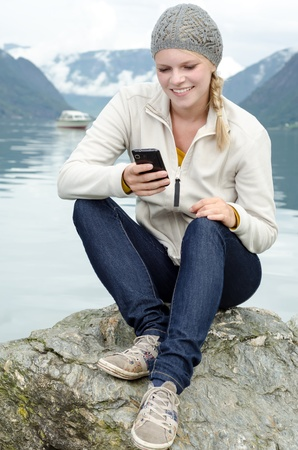 young blond woman with her Smartphone in the hand and a fjord in Norway in the background photo