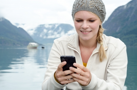 young blond woman with her Smartphone in the hand and a fjord in Norway in the background