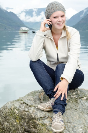 fleece: young blond woman called up with her Smartphone with a fjord in Norway in the background