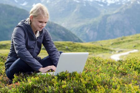 young blonde woman sits with laptop in alpine meadow before mountain landscape