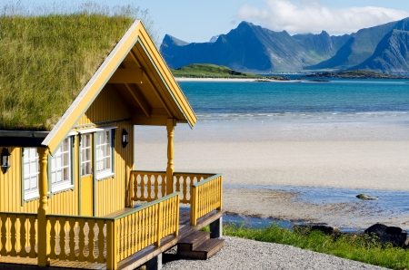 fishing huts: a yellow summer cottage on the beach on the Lofoten