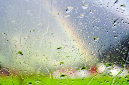 eau de pluie: Gouttes de pluie sur une vitre avec des paysages et arc en ciel en arri�re-plan Banque d'images