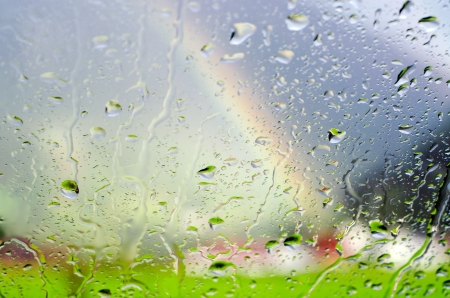 Raindrops on a glass panel with scenery and rainbow in the background Stock Photo