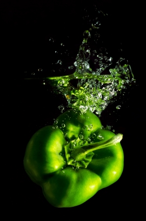 green pepper falls in the water before black background photo