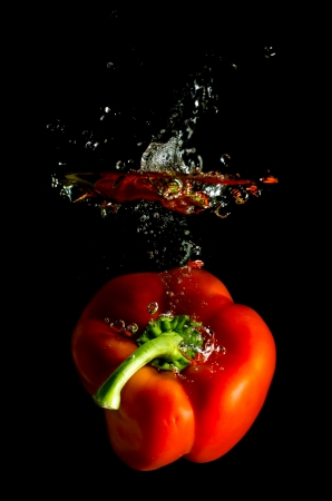 wellness background: red pepper falls in the water before black background