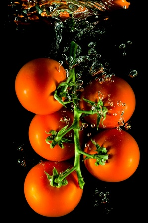 fruity salad: many tomatoes falling into water before black background