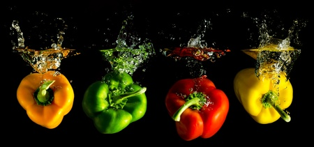 a panorama: four several coloured paprika falling into water before black background Stock Photo