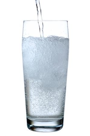 vaso de agua: un vaso lleno de agua mineral antes de fondo blanco