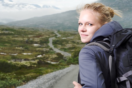 happily: young blond woman hiking with scenery in the background