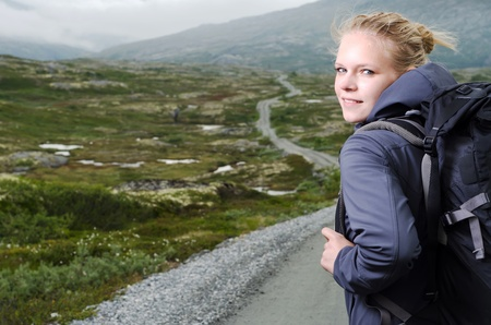 young blond woman hiking with scenery in the background photo