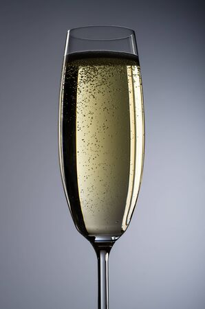 solemnity: a full champagne glass before grey background Stock Photo