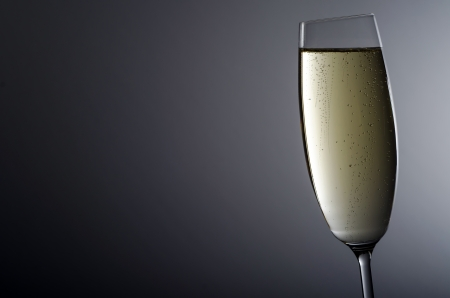 to stumble: a full champagne glass before grey background Stock Photo