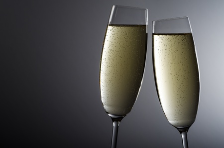 two filled champagne glasses before grey background