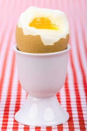 openly: a breakfastt egg in a eggcup on red checked table cover
