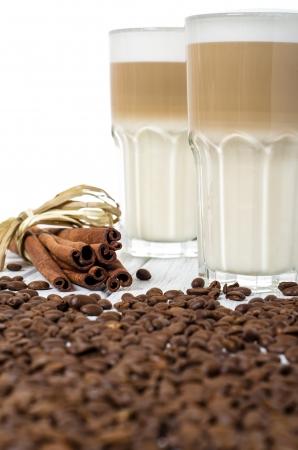 latte macchiato: latte macchiato in a glass with coffee beans and cinnamon sticks Stock Photo