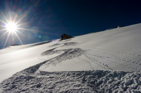 a ski track goes downhill with sun in the background Stock Photo - 17049300