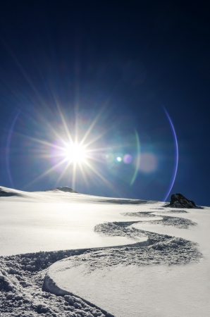 deep powder snow: a ski track goes downhill with sun in the background