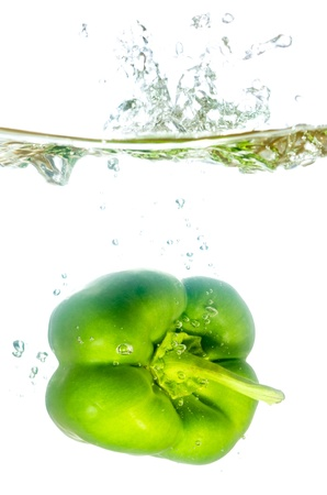 vital: green paprika pepper splashes into water before white background Stock Photo