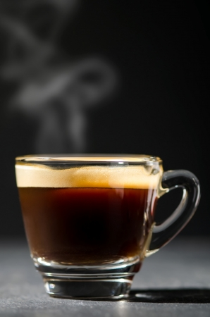 espresso in a glas steaming before dark background photo