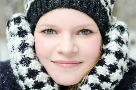 winter wood: young blond woman smiles with checked beanie and checked scarf in the winter wood Stock Photo