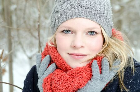 coldly: young blond woman smiles with grey beanie and orange scarf in the winter wood Stock Photo