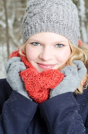 winter wood: young blond woman smiles with grey beanie and orange scarf in the winter wood Stock Photo