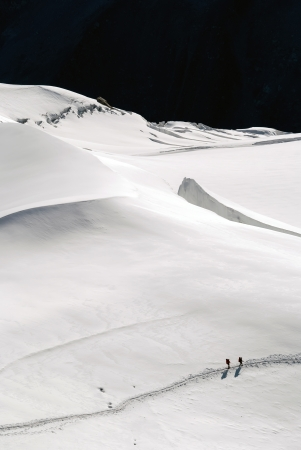 flatly: people walk on a glacier in the mountains