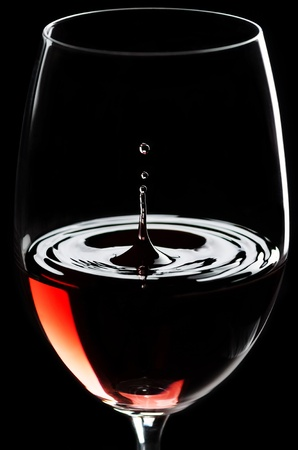 Red wine drips in a wineglass before black background photo