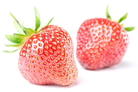 fruity salad: two red strawberries isolated before white background