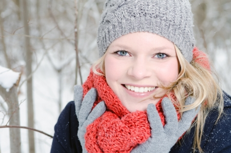 young blond woman smiles with grey beanie and orange scarf in the winter wood photo