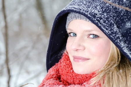 nicely: young blond woman smiles with grey beanie and orange scarf in the winter wood Stock Photo