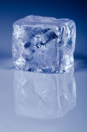 icily: ice cube with copy space below before blue background Stock Photo