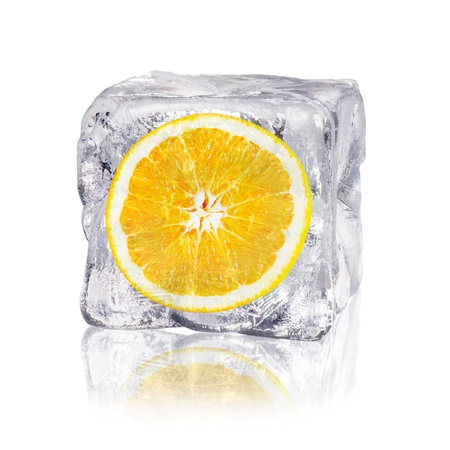 icily: a orange enclosed in an ice cube before white background Stock Photo