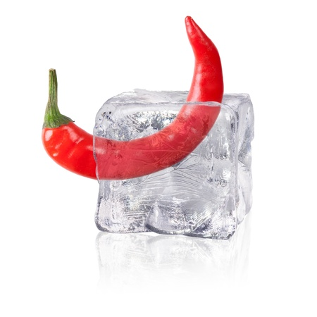 a chili enclosed in an ice cube before white background photo