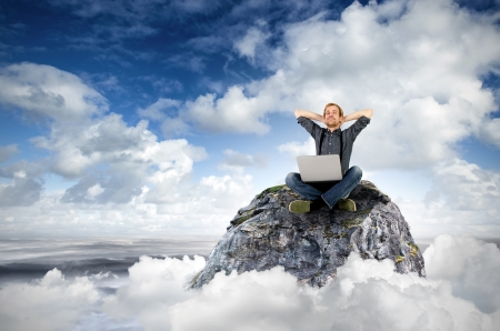 a man with laptop sits on a rock in the clouds photo